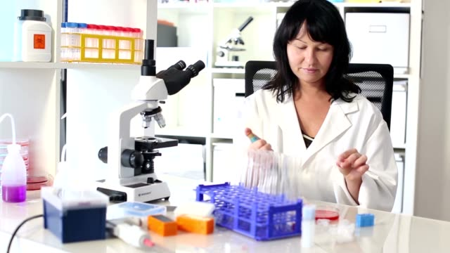woman with a pipette and a microscope in a lab video