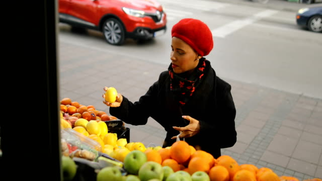 woman with a red hat choosing fruits on street market - mercato frutta donna video stock e b–roll