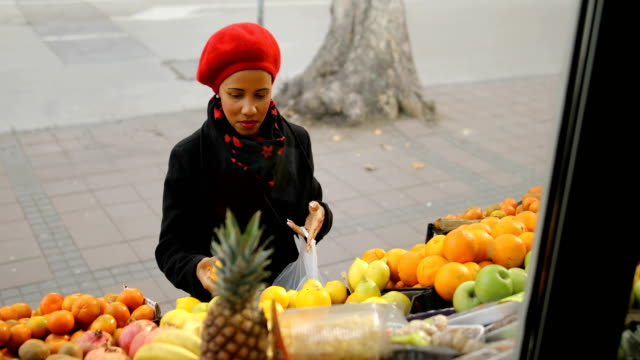 Woman with a red hat choosing fruits on street market video