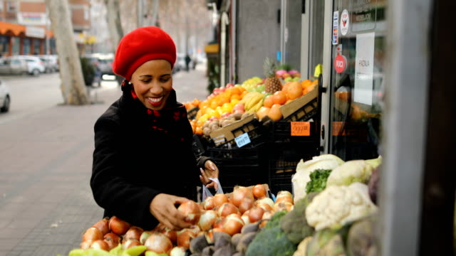Woman with a red hat choosing vegetables on street market video