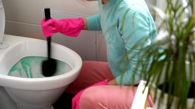 Woman with a rubber glove cleans a toilet bowl video