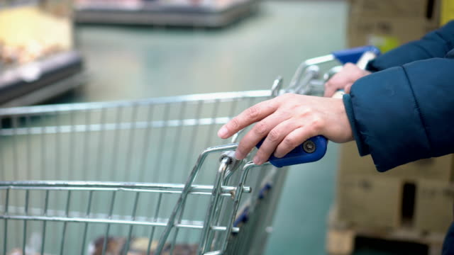 a woman with a shopping cart is standing in line at the store's checkout and nervously taps her finger on the cart. shopping at the supermarket. faceless. concept. 4k - simbolo concettuale video stock e b–roll