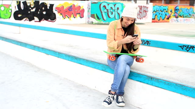 Woman with a Skateboard texting on her phone video