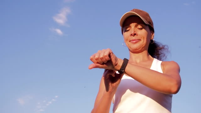 A woman with a smart watch goes in for sports. A woman with a smart watch goes in for sports. A woman is running around in the countryside. panting stock videos & royalty-free footage