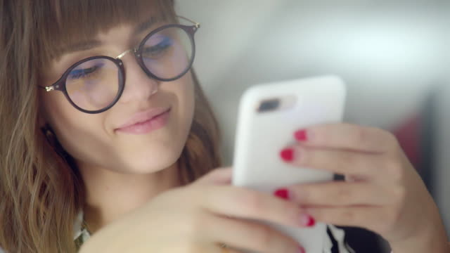 woman with a smile uses the phone: online shopping, social networks - inviare video stock e b–roll