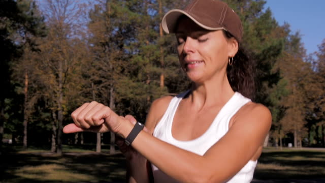 A woman with a sports gadget is engaged in fitness. A woman with a sports gadget is engaged in fitness. The girl is running around in the park. panting stock videos & royalty-free footage