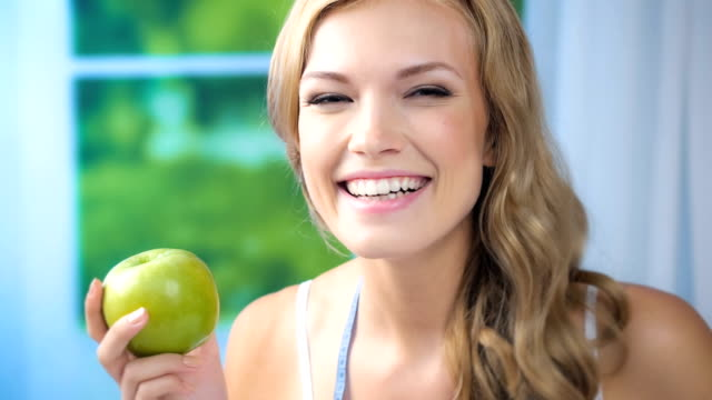 HD 1080@29,97: Woman with apple and measure tape, indoors video