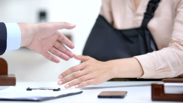 Woman with arm sling shaking lawyers hand, compensation after medical negligence Woman with arm sling shaking lawyers hand, compensation after medical negligence satisfaction stock videos & royalty-free footage