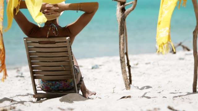 kvinna med armar bakom huvudet sitter i teak stol läsa en bok om tropisk strand - sarong bildbanksvideor och videomaterial från bakom kulisserna
