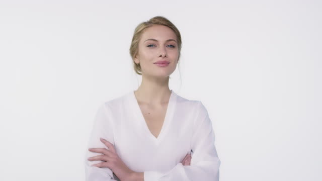 Woman with arms crossed against white background - vídeo
