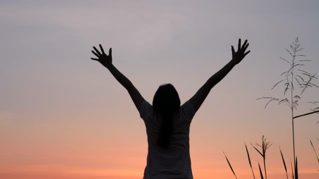 woman with arms raised  looking at sunset view - podnosić filmów i materiałów b-roll