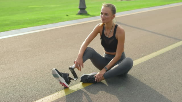 Woman with artificial limb sitting on road. Girl relaxing after training in park Smiling woman with artificial limb sitting on road. Cheerful girl relaxing after training in park. Fit lady in sportswear taking break after workout outdoors in slow motion artificial limb stock videos & royalty-free footage