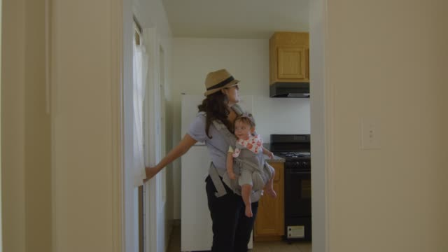 Woman with baby looking around an empty apartment video