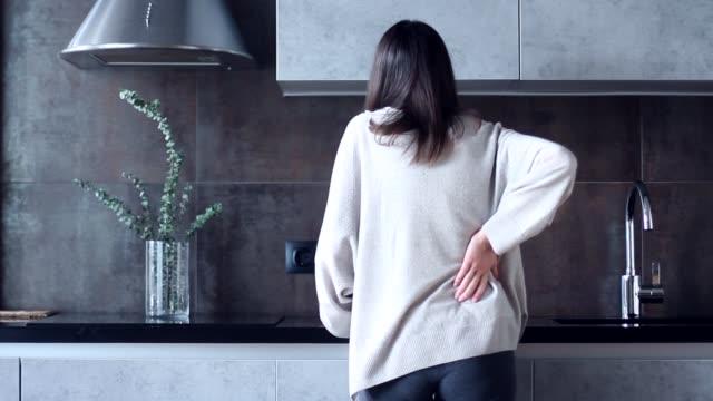 woman with backache in kitchen - dorsale video stock e b–roll