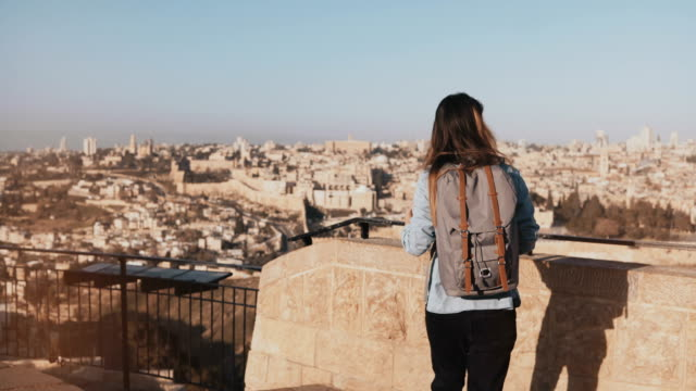 Woman with backpack comes up to Jerusalem panorama. Excited Caucasian tourist looks at ancient old town in Israel. 4K video