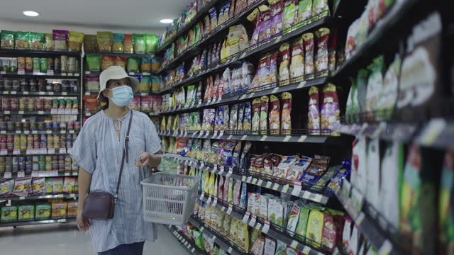Woman with basket in department store Asian woman in protective face mask during covid-19 pandemic shopping in department store snack aisle stock videos & royalty-free footage