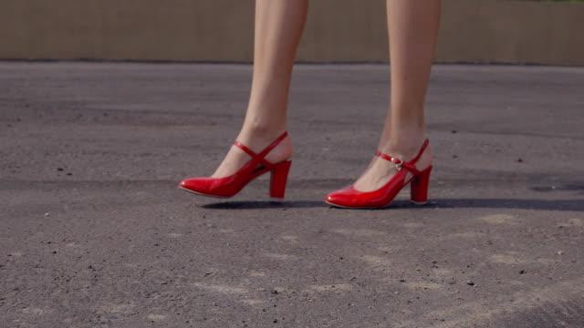 stockvideo's en b-roll-footage met vrouw met mooie benen in rood lakleer sandalen wandelen langs het asfalt - street style