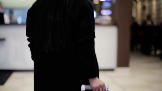 Woman with big red suitcase goes to reception at hotel video