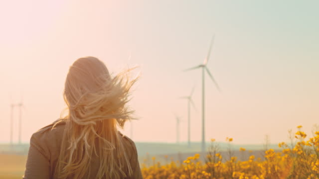 super slo mo - time warp effect woman with blond long hair running along wind turbines - risorse sostenibili video stock e b–roll