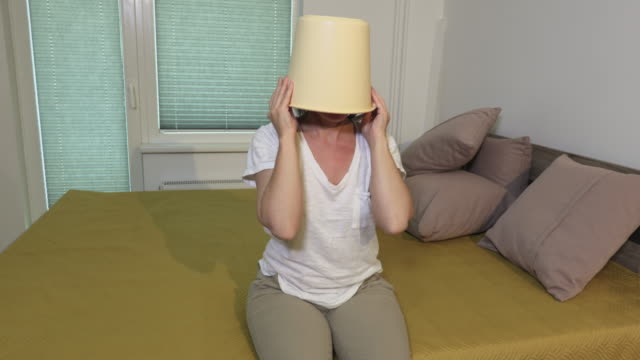 Woman with bucket on head at home - vídeo