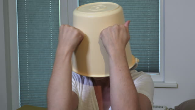 Woman with bucket over head hiding - vídeo