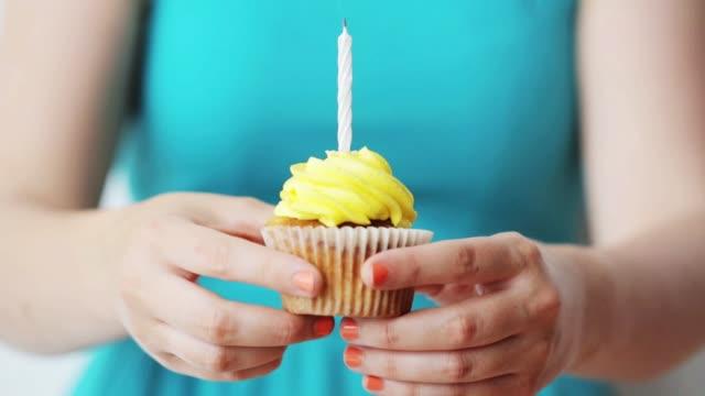 誕生日ケーキのろうそくを燃焼を持つ女性 - カップケーキ点の映像素材/bロール