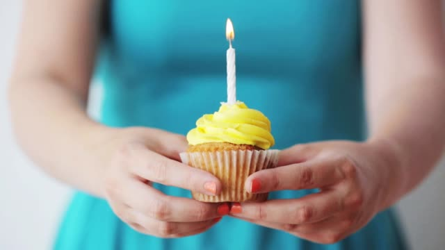 woman with burning candle on birthday cupcake - годовщина стоковые видео и кадры b-roll