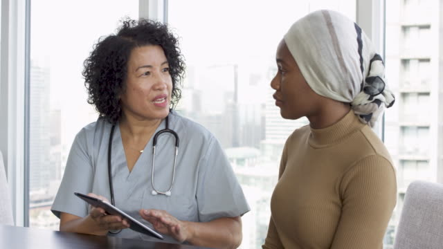 Woman with cancer meeting with female physician A young black woman with cancer is consulting her doctor of Asian descent. She is wearing a bandana to hide her hair loss. The two individuals are seated at a table together. The female doctor is holding a digital tablet. The patient is listening carefully to the physician's advice for treatment. cancer patient stock videos & royalty-free footage