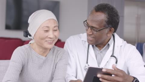 vidéos et rushes de femme avec le cancer analyse les résultats de test avec le médecin - courage