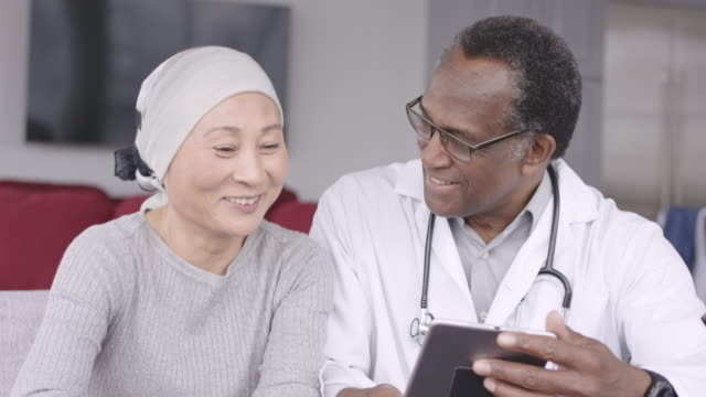 Woman with cancer reviews test results with doctor A Korean woman with cancer is meeting with her doctor. The doctor is showing her test results on an electronic wireless tablet. The doctor smiles as he gives good news regarding the patient's treatment. cancer patient stock videos & royalty-free footage