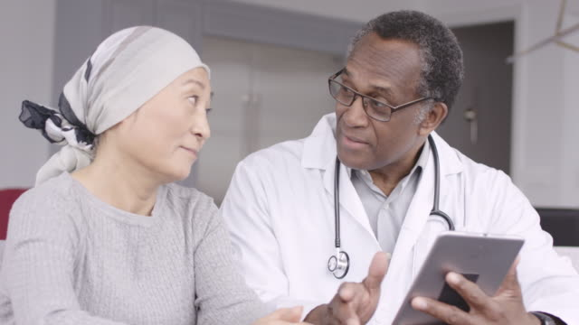 Woman with cancer reviews test results with doctor A Korean woman with cancer is meeting with her doctor. The doctor is showing her test results on an electronic wireless tablet. The doctor smiles as he gives good news regarding the patient's treatment. mammogram stock videos & royalty-free footage