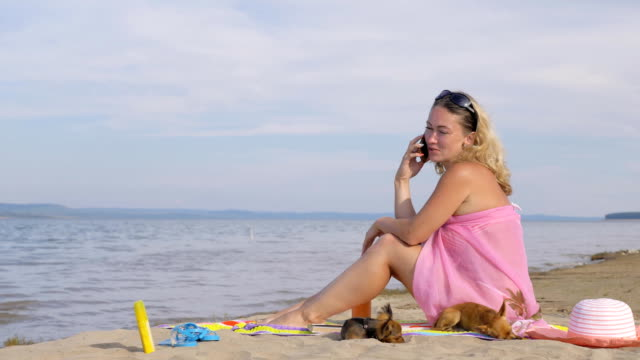 Woman with cell phone on the beach.