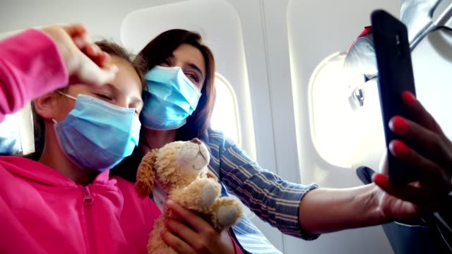 woman with child, in protective masks, communicating on video call via smartphone device. taking video or making selfie, while sitting inside airplane. flights opened after coronavirus epidemic - pasażer filmów i materiałów b-roll