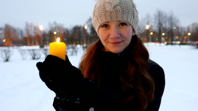Woman with Christmas candle, outdoor portrait, winter snowy park video