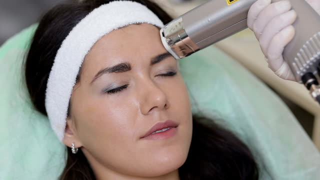 Woman with closed eyes getting photo rejuvenation procedure in a beauty salon.Cosmetician perfiming photo rejuvenation cosmetology procedure for a woman.Skin care. Young woman receiving facial beauty video