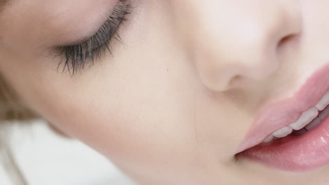 Woman with closed eyes touching her skin