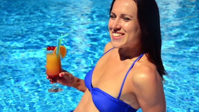 kobieta z koktajl w basenie. - 20 29 lat filmów i materiałów b-roll