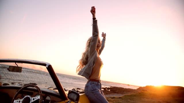 vidéos et rushes de femme avec voiture décapotable relaxante au bord de la mer au coucher du soleil - mode de la plage