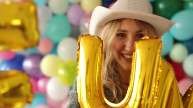 Woman with cowboy hat having fun in room full of balloons