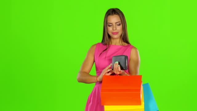 Woman with credit card and shopping bags. Green screen Attractive happy woman with credit card and shopping bags, young girl opens the purse and pulls out a golden card, on a green background gold card stock videos & royalty-free footage