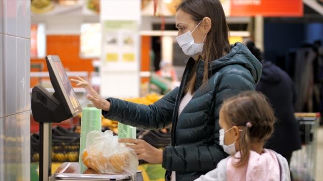 의료 마스크에 딸을 가진 여자는 슈퍼마켓에서 저울에 무게 오렌지 - 쇼핑 스톡 비디오 및 b-롤 화면