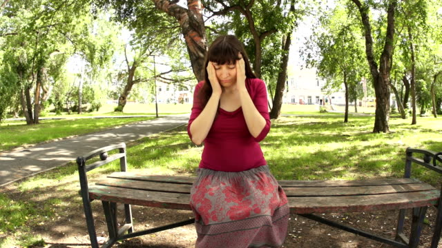 A woman with depression and a headache sitting in the park stroking whiskey video