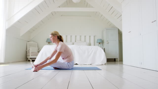 Woman With Digital Tablet Sitting In Bedroom Doing Yoga video