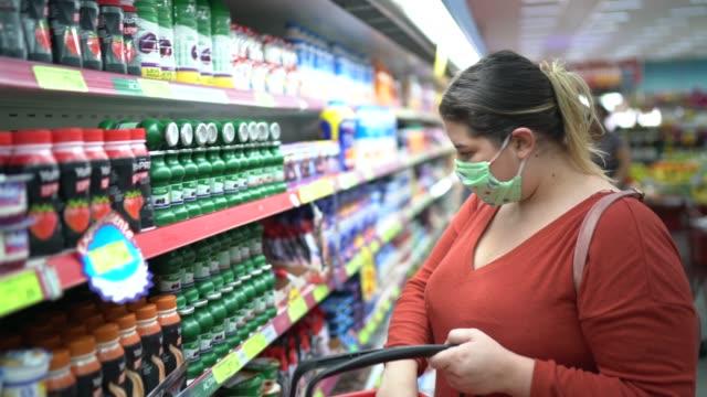 frau mit einweg-medizinmaske einkaufen im supermarkt - supermarkt einkäufe stock-videos und b-roll-filmmaterial