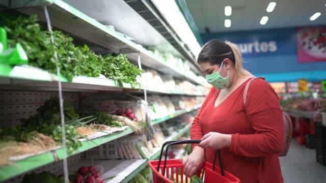 vídeos de stock e filmes b-roll de woman with disposable medical mask shopping in supermarket - supermarket worker
