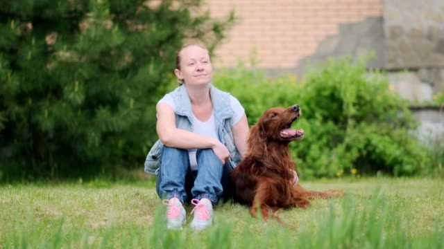 woman with dog sitting on green lawn near country house