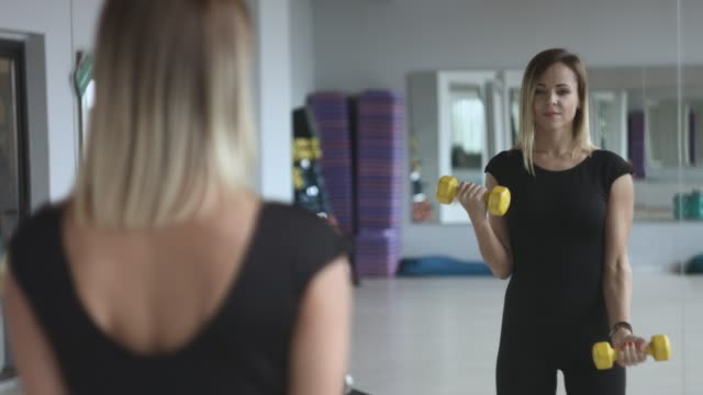 Woman with dumbbells in sport centre, in front of a mirror. 4K