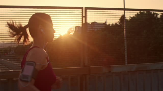 SLO MO TS Woman with earphones running at sunset Slow motion medium tracking shot of a woman with earphones listening to music and running at sunset across a highway overpass. healthy lifestyle stock videos & royalty-free footage