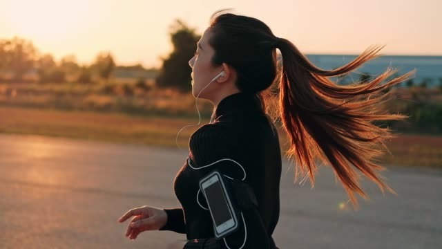 woman with earphones running in the sunset time(slow motion) - adrenalina video stock e b–roll