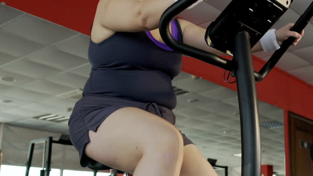 Woman with excess weight and cellulite legs working out on stationary bike video